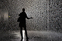 London, UK. 03.10.2012. Random International's experimental, interactive artwork RAIN ROOM opens to the public in The Curve art gallery space at The Barbican Centre. Picture shows: A visitor in the Rain Room. Photo credit: Jane Hobson.