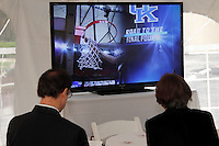 Patrons are able to keep track of the basketball games in the sports lounge tent during the 13th Annual ArtsGala at Wright State University's Creative Arts Center, Saturday, March 31, 2012.