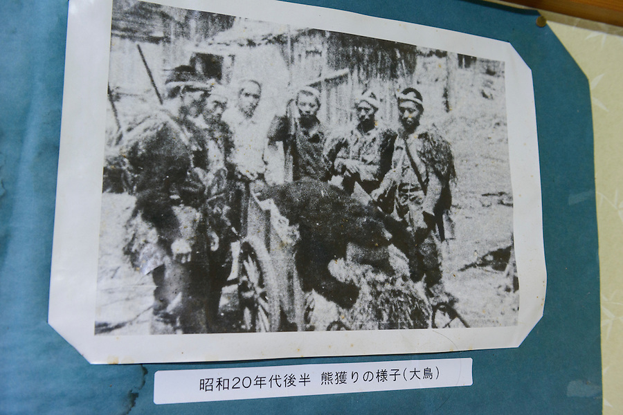 "A photograph on the wall of the Ashiya guesthouse  showing ""matagi"" bear hunters. Tsuruoka, Yamagata Prefecture, Japan, April 9, 2016. The city of Tsuruoka in Yamagata Prefecture is famous for its sansai mountain vegetable cuisine. These foraged grasses, fungi and vegetables are also used by the mountain ascetics of the Shugendo religion."
