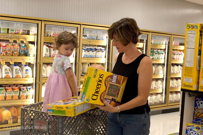 Berkeley CA Mother discussing choice of cereal with three-year-old daughter while grocery shopping  MR
