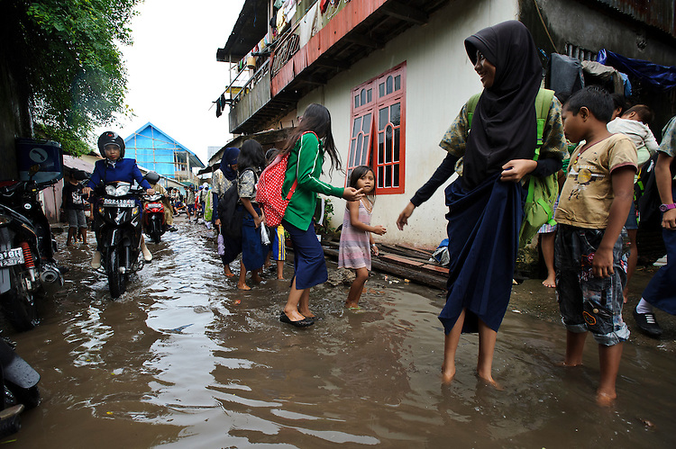 School children wading in a flooded street outside their school, Tallo, Makassar, Sulawesi, Indonesia.