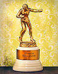 "A vintage golden colored boxer trophy with an inscription that reads ""Winner Main Event"" sets in front of a weathered wallpaper background."