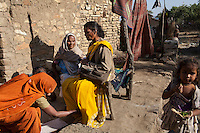 A village woman touches Shanti Adivasi's (in yellow saree), 52, feet as a prominent mark of extreme respect as Shanti chats with elderly villagers in a remote tribal village in Manikpur, Chitrakoot, Uttar Pradesh, India on 6th December 2012.  Shanti used to be a wood gatherer, working with her parents since she was 3, and later carrying up to 100 kg of wood walking 12km from the dry jungle hills to her home to repack the wood which sold for 3 rupees per kg. After learning to read and write in an 8 month welfare course, at age 32, she became a reporter, joining Khabar Lahariya newspaper since its establishment in 2002, and making about 9000 rupees per month, supporting her family of 14 as the sole breadwinner. Photo by Suzanne Lee for Marie Claire France.