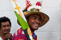"A Negros dancer holds his wooden machete in the religious procession in Atanquez (Sierra Nevada), Colombia, 3 June 2010. A colorful celebration of Corpus Christi is held in the Kankuamo Indians territory every year. ""The Dance of the Devils"" is an ancient tradition kept for centuries on the Colombia's Caribbean coast. This Christian religious event usually coincides with the summer solstice, which has always been the key point for the native cultures and for the black African slaves. Due to this confluence, the Kankuamo myths, the African animistic rites and other Pre-Columbian features have blended with the Spanish Catholic festival into a lively spectacle."