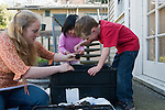 Berkeley CA Preschool teacher introducing four-year-olds, to use of worms to produce worm compost (vermicompost) and worm castings from decomposing food and plant waste in a worm bin  MR