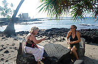 Two women tourists playing konane, or Hawaiian checkers, at Pu'uhonua o Honaunau (or City of Refuge), South of Kona, Big Island of Hawaii