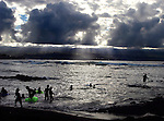 A late-day storm rolls in along from the ocean though nobody pays it any mind at Richardson Beach Park in Hilo on the Big Island of Hawaii.