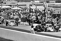 HAMPTON, GA - APRIL 22: Johnny Rutherford (#4 McLaren M24B/Cosworth TC) leaves his pit box while the crew of Gordon Johncock (#20 Penske PC6/Cosworth TC) changes tires and adds fuel during the Gould Twin Dixie 125 event on April 22, 1979, at Atlanta International Raceway near Hampton, Georgia.