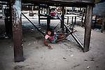 Bajau girl resting under his stilt house on Mabul Island