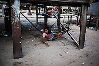 Bajau girl resting under his stilt house on Mabul Island