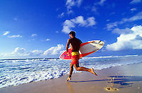 Man running out from the beach to surf with board in hand, North Shore