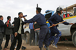 A police officer tells a man waiting to apply for a job in Kirkuk, Iraq to leave after a police recruiting drive was shut down amid allegations of bribery. Officials sought to fill 1,300 slots for the next training class, but were overwhelmed when more than 4,000 applicants showed up. More than half were turned away, and hundreds of others waited for hours but never got a chance to submit their papers. The event was shut down after a U.S. advisor observed an Iraqi recruiting officer take a bribe from an applicant. Desperate job seekers were ordered to disperse, but many refused, so police resorted to violence to force them from the grounds. Dec. 6, 2007. DREW BROWN/STARS AND STRIPES