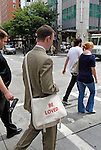"North America, USA, Washington, Seattle. Pedestrian with tote ""be loved""."