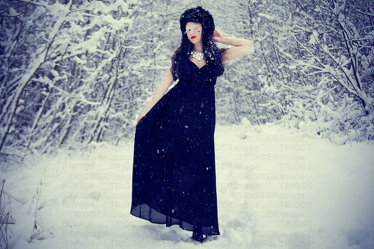 A pale girl with long black hair, dressed in a black gown, standing in a snowy forest.