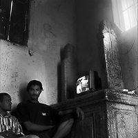 Cairo, Egypt, The City of the Dead, 2000 -  Young men escape from their undertaker duties and watch a television they have set up on a grave marker in a tomb.