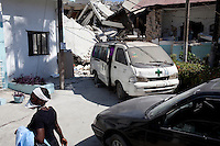 A woman walks past a collapsed building, which fell during the recent earthquake, at the St. Francois De Sales hospital in Port-au-Prince, Haiti.