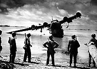 U.S. Army troops pause for a look at a Japanese seaplane during the battle of Makin.  The plane was under repair in the lagoon when the invasion started.  The Japanese used it as a machine gun nest until American fliers took care of it.  November 1943.  (Coast Guard)<br /> Exact Date Shot Unknown<br /> NARA FILE #:  026-G-3000<br /> WAR &amp; CONFLICT BOOK #:  1320