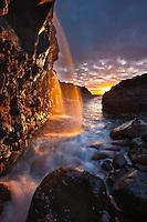Sunset illuminates the waterfall as it hits the ocean in Princeville, Kauai.
