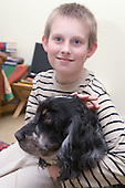 Boy with Autism stroking his pet dog. MR