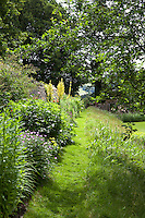 A mown grass path runs between a wild bank and a summer border at Haddon Hall