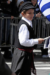 Greek Parade in New York City. A boy in traditional clothing and holding a Greek flag walks in the Greek Parade in New York City.