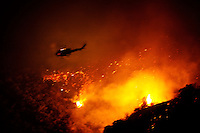 Santa Barbara, Calif., May 5, 2009 - A helicopter dumps its payload of water on  the Jesusita Fire in Mission Canyon north of Foothill Road. Firefighters and at least two helicopters continued to battle the blaze through the night. According to David Sadecki with the Santa Barbara County Fire Department, the fire began at around 1:45 pm today near the popular Jesusita Trail near Inspiration Point in San Roque Canyon. As of midnight more than 420 acres had burned and about 1,000 homes were evacuated, with about 2,000 threatened.