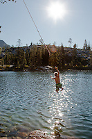 Boy dropping from a rope swing into Long lake, California.