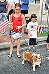 Freckled girl with spaniel dog, and young boy at Memorial Day Parade, Merrick, New York, USA, on May 30, 2011