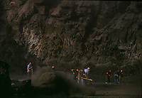 Small mountaintop removal site employes a small number of workers that are cleaning up what a large company left as rubble. Miners sweep rock off of coal to clean it before loading onto trucks.