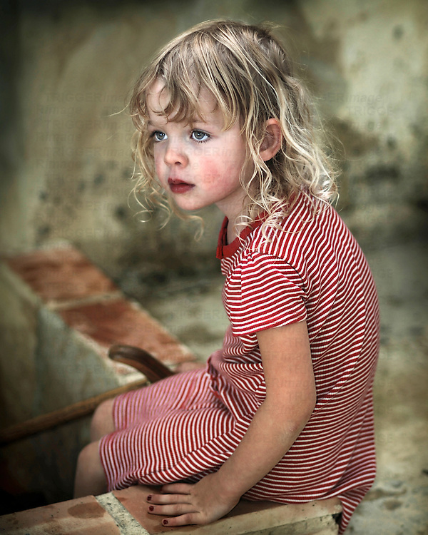 A young girl with blonde hair sitting on a low wall wearing a red and white striped summer dress