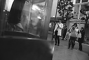 Pedestrians photograph a shop dummy hanging in a display case, Shibuya, Tokyo, Japan. 2004