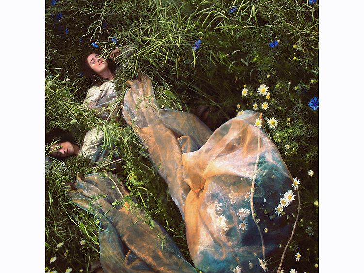 Two women laying on a meadow full of camomiles, dressed in vintage clothes and long veils, sleeping.