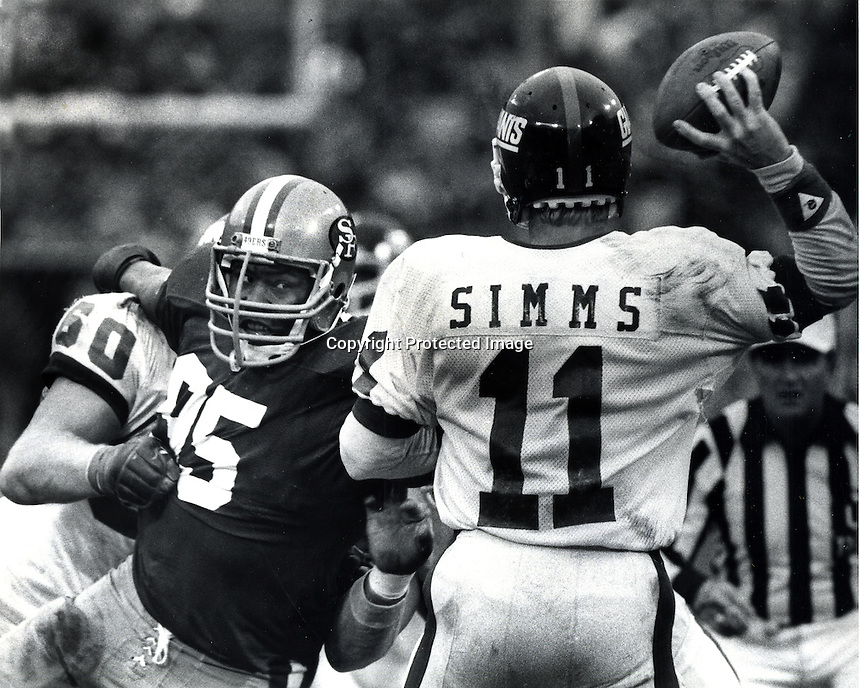 New York Giants quarterback Phil Simms gets big rush from San Francisco 49ers Michael Carter. <br />(1984 photo by Ron Riesterer)