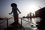 Uyen, 49, a boat taxi operator, rows through a river neighborhood on the Hau Giang River, a tributary of the Mekong River, in Long Xuyen, the capital of An Giang Province, Vietnam. Uyen has operated a boat taxi for almost 20 years. When the Mekong River reaches Vietnam it splits into two smaller riveres. The &quot;Tien Giang&quot;, which means &quot;upper river&quot; and the &quot;Hau Giang&quot;, which means &quot;lower river&quot;. Photo taken on Monday, December 8, 2009. Kevin German / Luceo Images