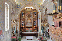 Sao Miguel Chapel, or St Michael's Chapel, designed in Manueline style 1517-22 by Marco Pires and completed by Diogo de Castilho, on the site of a 12th century chapel in the University of Coimbra, Coimbra, Portugal. In the chancel is the Mannerist altarpiece, designed by Bernardo Coelho in 1605 and made by sculptor Simon Mota, with paintings by Simon Rodrigues and Domingos Vieira Serrao. The chapel was renovated in the 17th and 18th centuries, with Manuel Ramos making the pulpit in 1684, ceiling painted by Francisco F de Araujo, tiled floor added 1613, Baroque organ with 2,000 pipes built 1733 by Fray Manuel de Sao Bento, and Gabriel Ferreira da Cunha painting chinoiserie elements in 1737. The University of Coimbra was first founded in 1290 and moved to Coimbra in 1308 and to the royal palace in 1537. The building is listed as a historic monument and a UNESCO World Heritage Site. Picture by Manuel Cohen