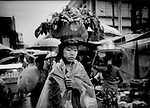 Young woman balances vegetables and flowers on her head in a driving monsoonal rain, Bago, Burma.
