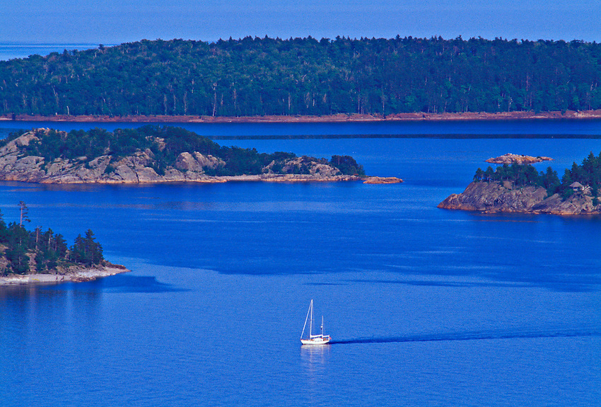 A sailboat cruises the waters of Lake Superior at Partridge Bay near Marquette, Michigan.