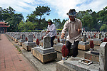 Two Vietnamese war veterans place incense on the graves of fallen comrades at Truong Son Martyrs Cemetery in Quang Tri province, Vietnam. The cemetery contains the graves of about 10,300 communist soldiers who died along the Ho Chi Minh Trail supply network into South Vietnam during the conflict from 1959 to 1975. April 24, 2013.