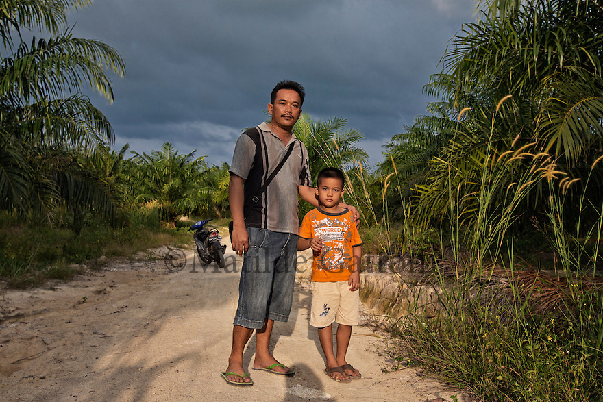 """Indonesia - Bangka Island - Rebo - Ajong Fang, 45, and his son Feri, 6 standing in their palm plantation. Ajong owns a mine and has worked on tin mining for ten years now. He extracts 200 kg of pure tin per day from his concession. He has also reclamated a 50-hectare previous mining concession, turning it into a palm oil plantation. """"I did it for my children"""" he says, """"because tin mining will not be profitable in the long term""""."""