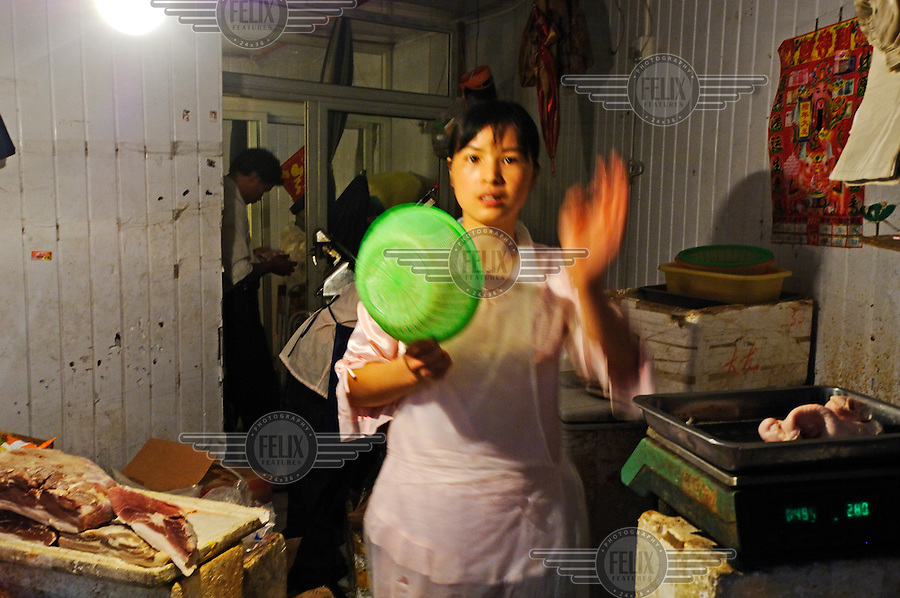 Woman working in Dajing Lu market in Shanghai's old Chinese city, one of the city's oldest and busiest wet markets.