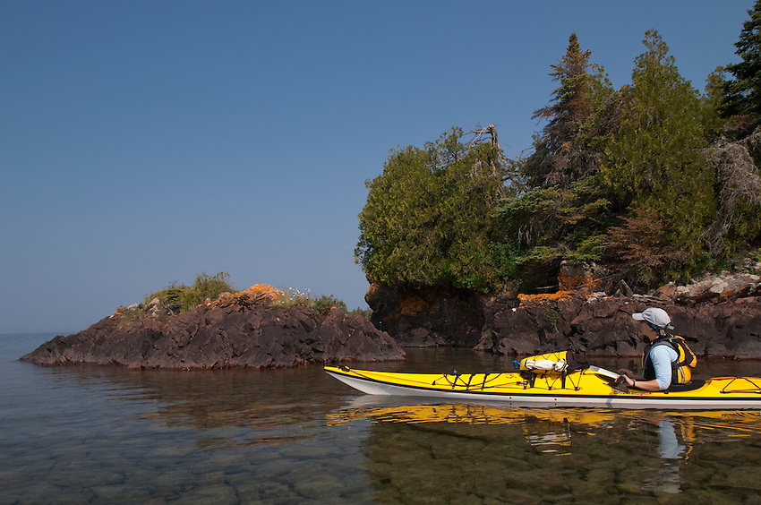 A sea kayaker explores the Five Finger Bay area of Isle Royale National Park.