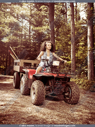 Young farm woman gardener riding an ATV with a trailer along countryside road. Muskoka, Ontario, Canada.