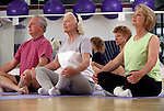 Senior man and women in Yoga class