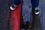 Young boy (2-4 yrs old) standing along curb with tennis shoes, and red curb with oil puddles on street, Everett, Washington USA