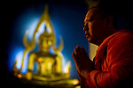 A Buddhist monk participates in afternoon prayers at Wat Benchamabophit (the Marble Temple) in Bangkok. The Marble Temple, so called because it was built of white Carrara marble from Italy, is the most modern of Bangkok's royal wats and a place of learning for academic-minded monks. Constructed during the reign of King Chulalongkorn (Rama V), Wat Benchamabophit means &quot;the temple of the Fifth King.&quot;