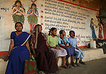 "A group of women and girls sit on a bench in Kokatnur, India. The mural behind them is part of an extensive public education campaign executed by MASS (a group of ex-Devadasis) and supported by its umbrella organization, MYRADA, and includes large painted murals around Yellamma temples with text and pictures warning against participating in the Devadasi system.  These murals depict scenes of various Devadasi dedication rituals with large ""X"" marks through them.  While many of Yellamma's worshippers are illiterate, the paintings, with their vivid colors and the dramatic scenes they depict, are compelling.  Coupled with other forms of public education, the hope is that Devadasi dedications will become a thing of the past."