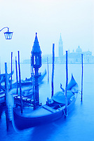 Italy, Venice. Gondola and San Giorgio  Maggiore in blue tones. Gondolas moored at Molo San Marco at dusk.