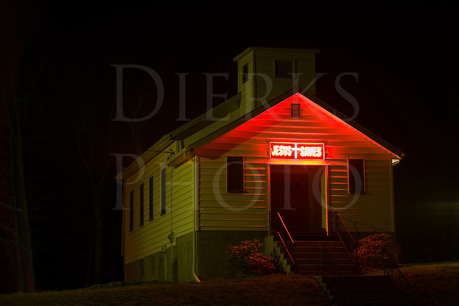 """Red neon """"Jesus Saves"""" sign above a church door glowing in the dark night, the Bible Belt in Pennsylvania, PA, USA."""