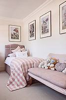 A girl's bedroom with a single bed dressed with furnishings in shades of pink in striped and check patterns. A collection of illustrations of fairies hang on the wall.