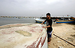 A Palestinian fisherman fixes his boat in the port of Gaza City on March 31, 2013. An Israeli military spokesman announced on March 21, that the Israeli military will again reduce the permitted fishing range in the Gaza Strip from six nautical miles to three (approximately 5.5 kilometres), in response to missile fire by armed Palestinian groups towards the south of Israel earlier that morning. Photo by Emad Nassar